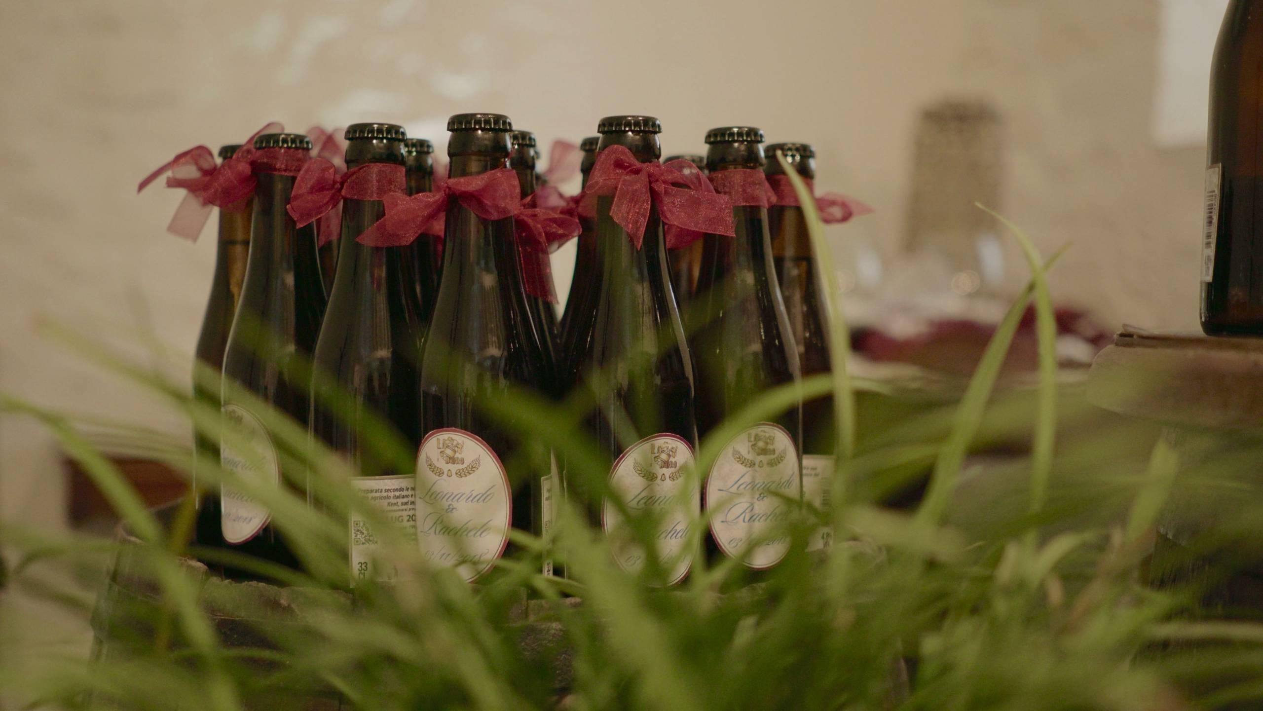 foto da dietro una pianta di bottiglie di birra con etichette personalizzate e infiochettate