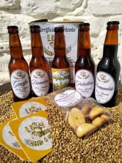 foto dall'alto delle 5 birre da '33 sopra una montagnetta di orzo con un pacchetto di biscotti di birra guelfa
