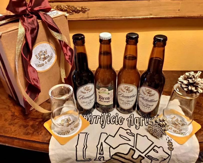 foto delle quattro birre sopra un tavolo sopra uno shopper con il logo stampato sopra
