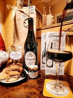 foto di un tavolo allestito con biscotti alla birra romualda e un bicchiere dove si sta versando la suddetta
