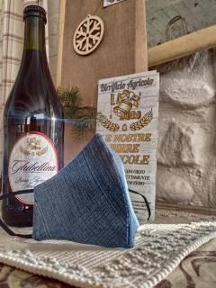 foto di una mascherina con tema jeans sopra un tavolo accanto ad una birra ghibellina da '33