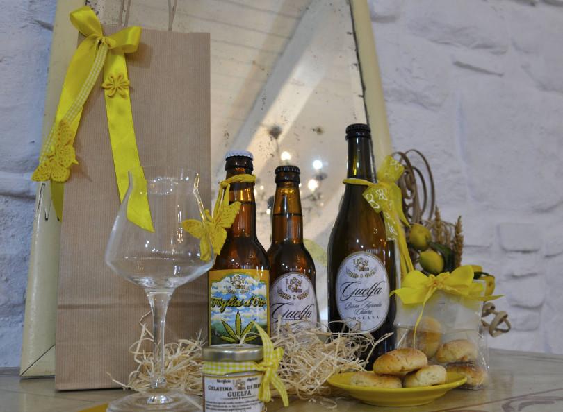 3 birre, 1 bicchiere, 1 gelatina e un pacchetto di biscotti sopra un tavolo addobbato