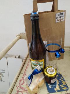 foto di birra, bicchiere, sottobicchiere e shopper sopra un tavolino