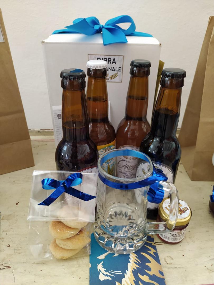 foto di 4 birre da 33, bicchiere, sottobicchiere e shopper, gelatina sopra un tavolino